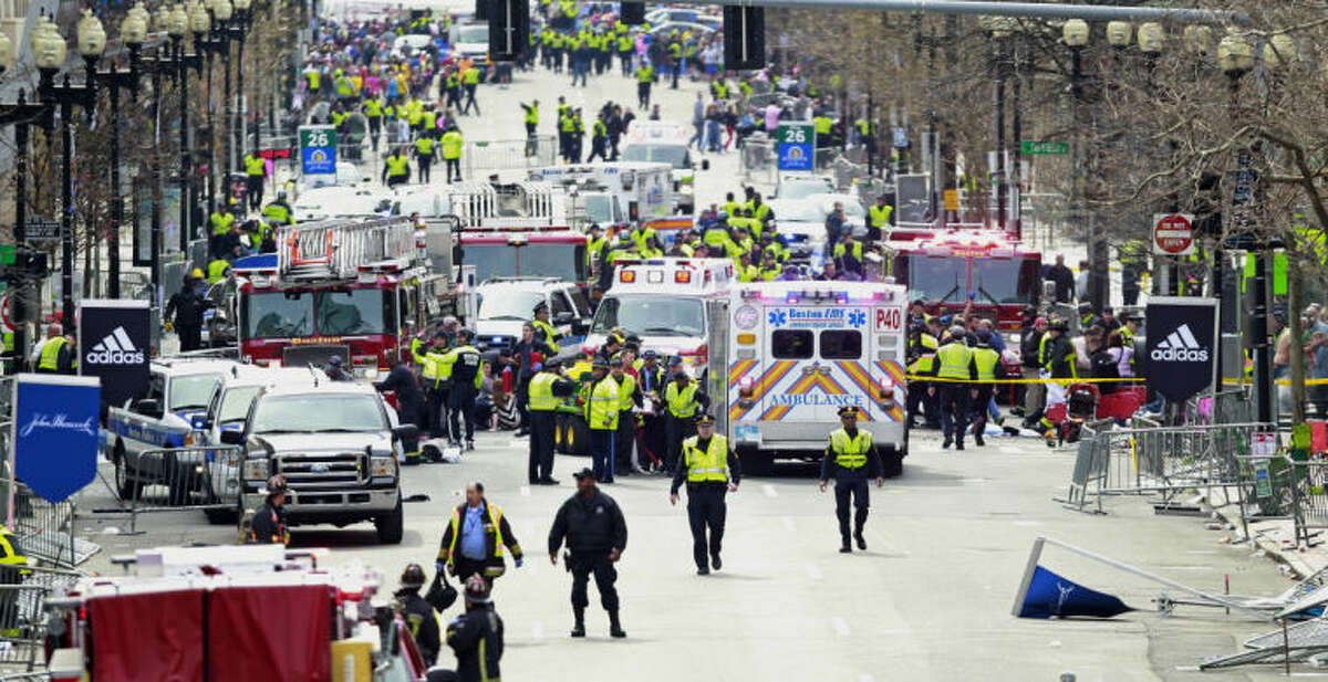 Police clear the area at the finish line of the 2013 Boston Marathon as medical workers help injured following explosions in Boston, Monday, April 15, 2013. The explosions near the finish of the Boston Marathon on Monday, killied at least two people, injuring over 20 others. (AP Photo/Charles Krupa)