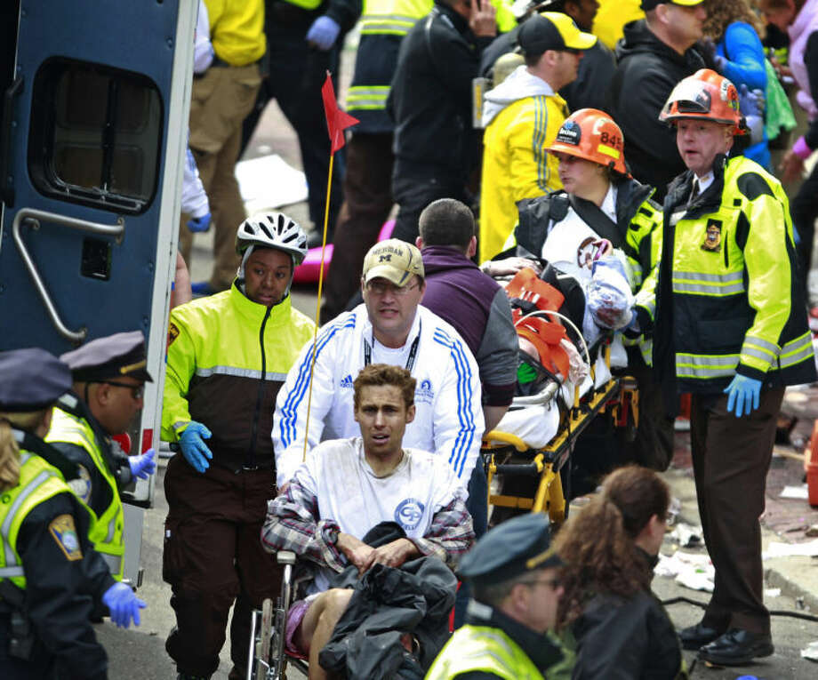 Medical workers aid injured people at the finish line of the 2013 Boston Marathon following an explosion Monday, April 15, 2013 in Boston. Two bombs exploded near the finish line of the marathon on Monday, killing at least two people, injuring at least 22 others and sending authorities rushing to aid wounded spectators. (AP Photo/Charles Krupa)