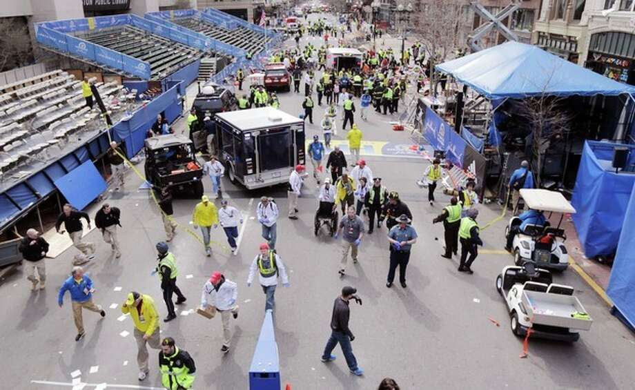 Police clear the area at the finish line of the 2013 Boston Marathon following an explosion in Boston, Monday, April 15, 2013. Two explosions shattered the euphoria of the Boston Marathon finish line on Monday, sending authorities out on the course to carry off the injured while the stragglers were rerouted away from the smoking site of the blasts. (AP Photo/Charles Krupa) / AP