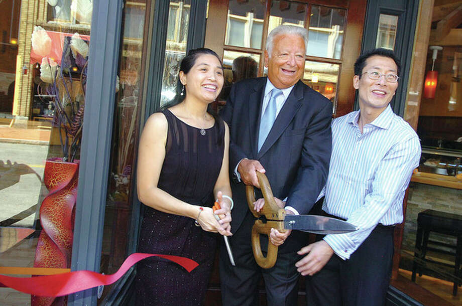 Hour photo/ Alex von KleydorffNorwalk Mayor Richard A. Moccia is flanked by Sophia Lin and John Jiang, owners of Shanghai Asian Bistro in SoNo, during a grand opening ceremony held Wednesday. / 2012 The Hour Newspapers