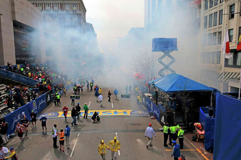Medical workers aid injured people at the 2013 Boston Marathon following an explosion in Boston, Monday, April 15, 2013. Two explosions shattered the euphoria of the Boston Marathon finish line on Monday, sending authorities out on the course to carry off the injured while the stragglers were rerouted away from the smoking site of the blasts. (AP Photo/The Boston Globe, David L Ryan) / The Boston Globe