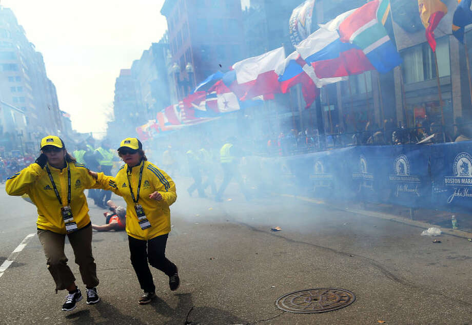 People react to an explosion at the 2013 Boston Marathon in Boston, Monday, April 15, 2013. Two explosions shattered the euphoria of the Boston Marathon finish line on Monday, sending authorities out on the course to carry off the injured while the stragglers were rerouted away from the smoking site of the blasts. (AP Photo/The Boston Globe, John Tlumacki)