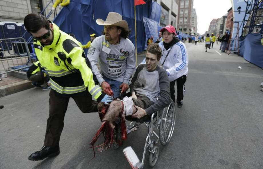 EDS NOTE: GRAPHIC CONTENT - Medical workers runs an injured man past the finish line the 2013 Boston Marathon following an explosion in Boston, Monday, April 15, 2013. Two explosions shattered the euphoria of the Boston Marathon finish line on Monday, sending authorities out on the course to carry off the injured while the stragglers were rerouted away from the smoking site of the blasts. (AP Photo/Charles Krupa)