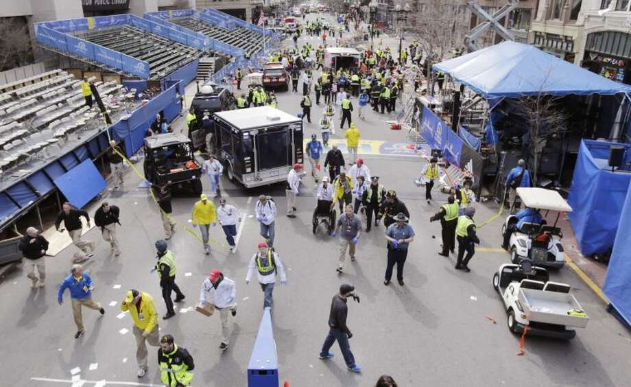 Police clear the area at the finish line of the 2013 Boston Marathon following an explosion in Boston, Monday, April 15, 2013. Two explosions shattered the euphoria of the Boston Marathon finish line on Monday, sending authorities out on the course to carry off the injured while the stragglers were rerouted away from the smoking site of the blasts. (AP Photo/Charles Krupa)