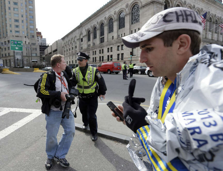Boston police ask people to leave the area in Copley Plaza in the aftermath of two blasts which exploded near the finish line of the Boston Marathon in Boston Monday, April 15, 2013. (AP Photo/Elise Amendola)