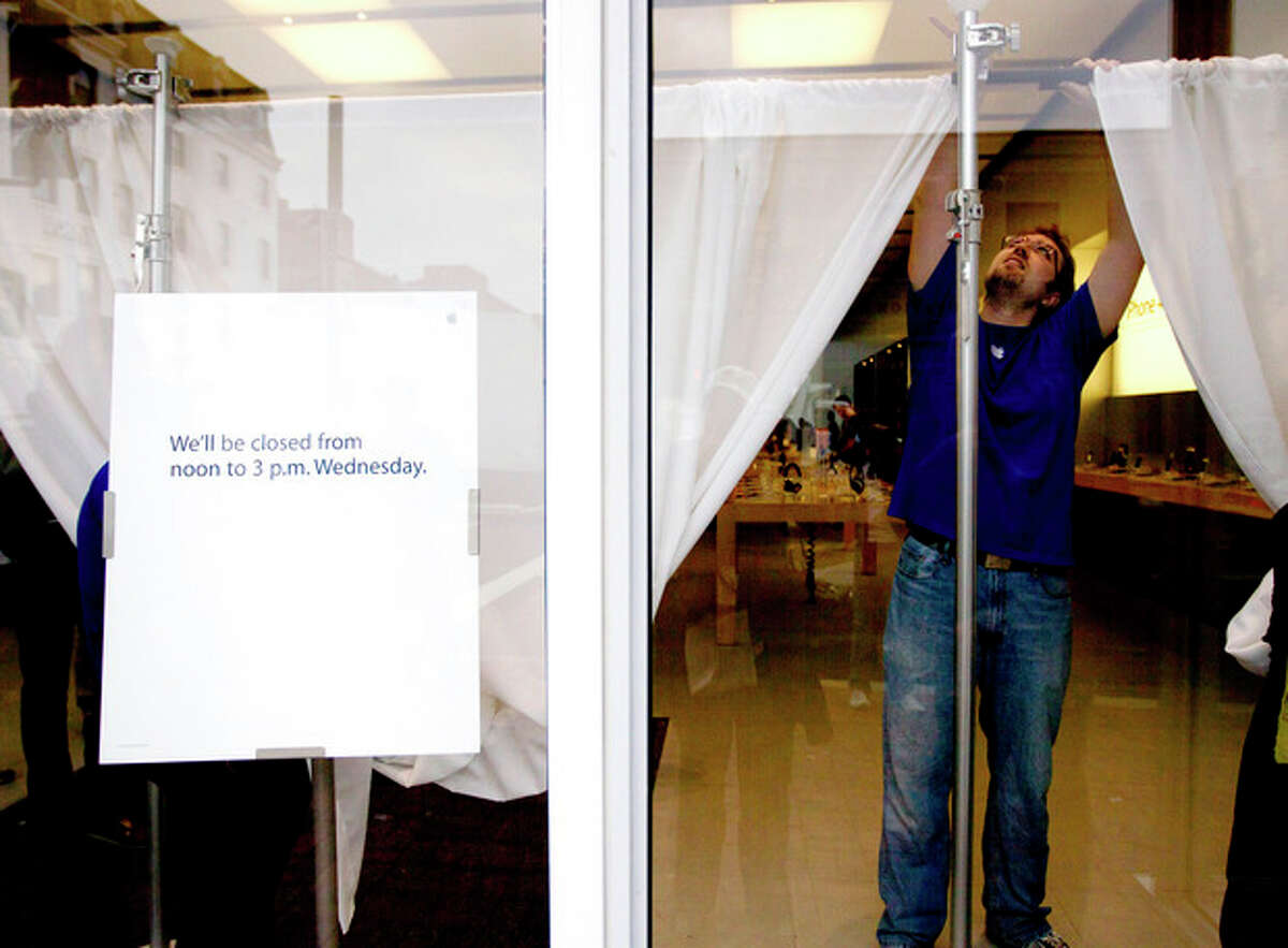 An Apple store employee hangs white curtains in the front window of a closed store in Washington, Wednesday, Oct. 19, 2011, to obstruct the inside view. Apple closed a number of its stores for a memorial service for co-founder and CEO Steve Jobs. Jobs passed away Oct. 5, 2011, of pancreatic cancer. (AP Photo/Carolyn Kaster)