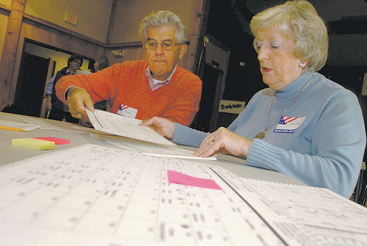 Volunteers Dick Martin and Paula Byrdy assist the Registrars of Voters Office last year while conducting an audit of Wilton's District 2 election results, as per state requirement. File photo / Erik Trautmann