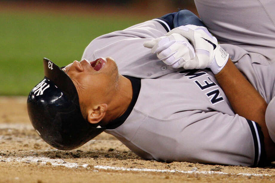 New York Yankees' Alex Rodriguez rolls on the ground after being hit by a pitch in the eighth inning of a baseball game against the Seattle Mariners, Tuesday, July 24, 2012, in Seattle. Even as Rodriguez writhed on the ground in pain, he didn't believe his left hand was fractured. Turns out A-Rod was wrong, and now the Yankees will be without another of their star players. (AP Photo/Kevin P. Casey) / FR132181 AP