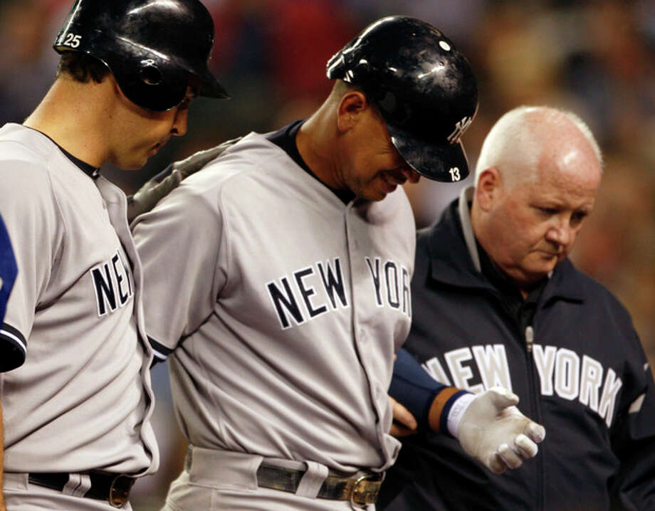 New York Yankees' Alex Rodriguez, center, is escorted by teammate Mark Teixeira, left, and an unidentified person, right, as he leaves the game in the eighth inning after being hit by a pitch during a baseball game against the Seattle Mariners, Tuesday, July 24, 2012, in Seattle. Rodriguez broke his hand when he was hit by an 88 mph changeup from Felix Hernandez (AP Photo/Kevin P. Casey) / FR132181 AP