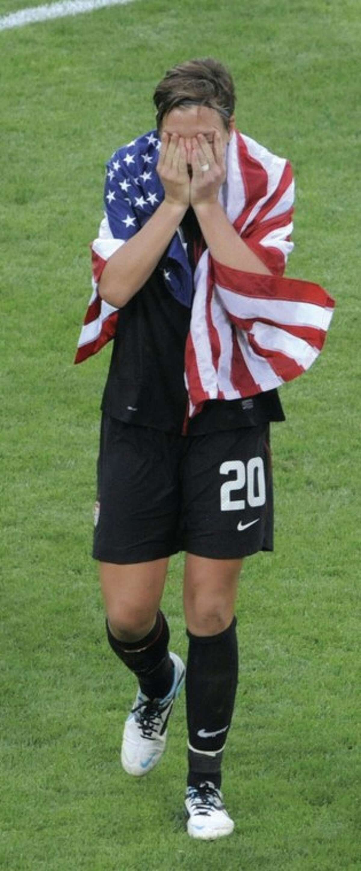 United States' Abby Wambach is wrapped in a US flag after her team won in a penalty shootout during the quarterfinal match between Brazil and the United States at the Women?•s Soccer World Cup in Dresden, Germany, Sunday, July 10, 2011. (AP Photo/Jens Meyer)