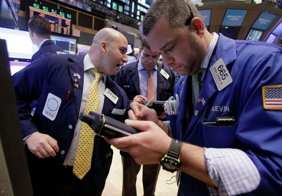 Trader Kevin Lodewick, right, works on the floor of the New York Stock Exchange Tuesday, Jan. 10, 2012. Stocks are shooting higher after the market opened on comforting news from Europe and an optimistic outlook from corporate bellwether Alcoa. (AP Photo/Richard Drew)