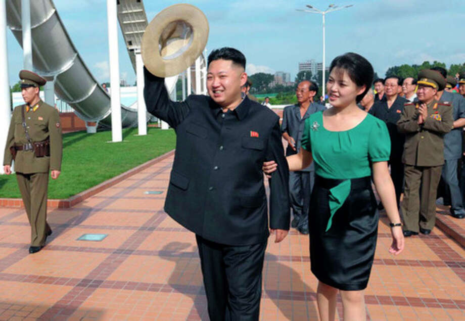 In this Wednesday, July 25, 2012 photo released by the Korean Central News Agency (KCNA) and distributed in Tokyo by the Korea News Service Thursday, July 26, 2012, North Korean leader Kim Jong Un, center, accompanied by his wife Ri Sol Ju, right, waves to the crowd as they inspect the Rungna People's Pleasure Ground in Pyongyang. (AP Photo/Korean Central News Agency via Korea News Service) JAPAN OUT UNTIL 14 DAYS AFTER THE DAY OF TRANSMISSION / KCNA via KNS