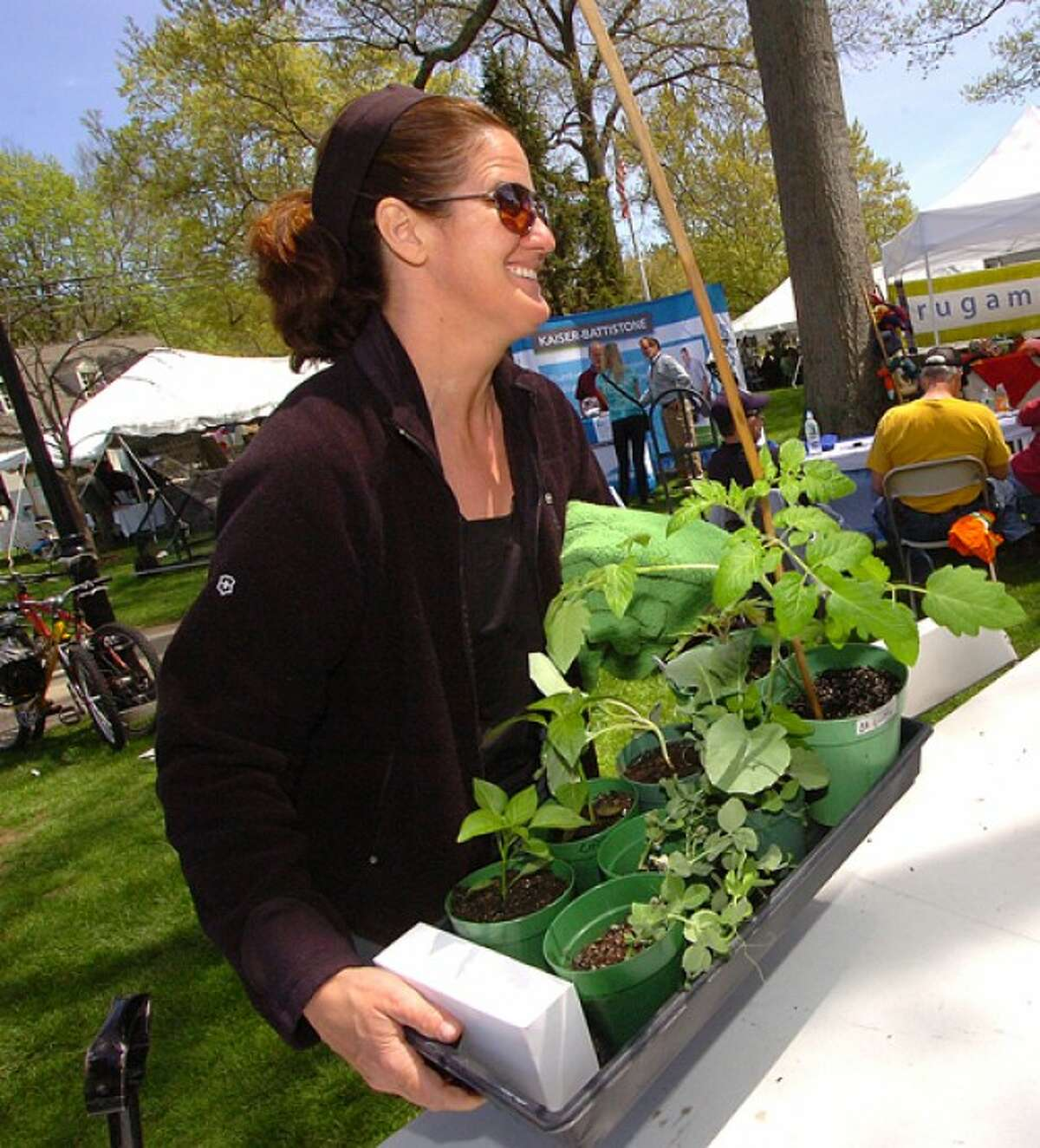 Photo/Alex von Kleydorff. Anne Koth buys some Tomatoes Peas and Peppers grown from seed by the Wilton High School Organic club in the schools greenhouse