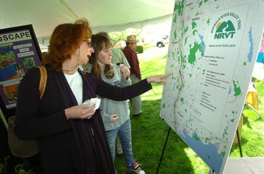 File Photo/Alex von Kleydorff. From left, Connie and Erin Cobb look at the map of the Norwalk River Valley Trail and its proposed bike path through Wilton.