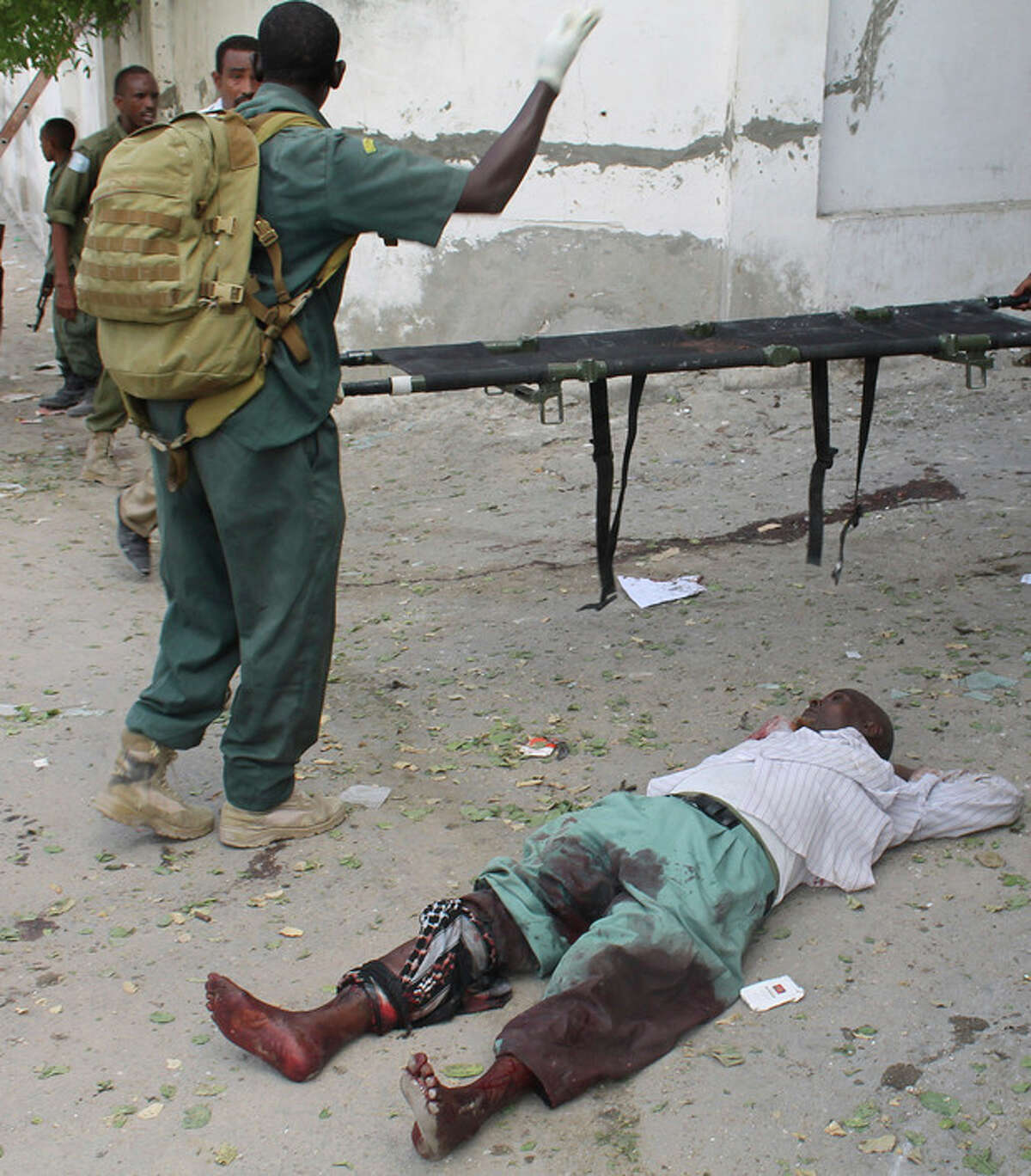 A Somali soldier stands over a wounded civilian lying at the entrance of Mogadishu?'s court complex after being injured during a siege by militants in Mogadishu, Somalia, Sunday, April 14, 2013. Militants launched a serious and sustained assault on Mogadishu's main court complex Sunday, detonating at least two blasts, taking an unknown number of hostages and exchanging extended volleys of gunfire with government security forces, witnesses said.(AP Photo/Farah Abdi Warsameh)