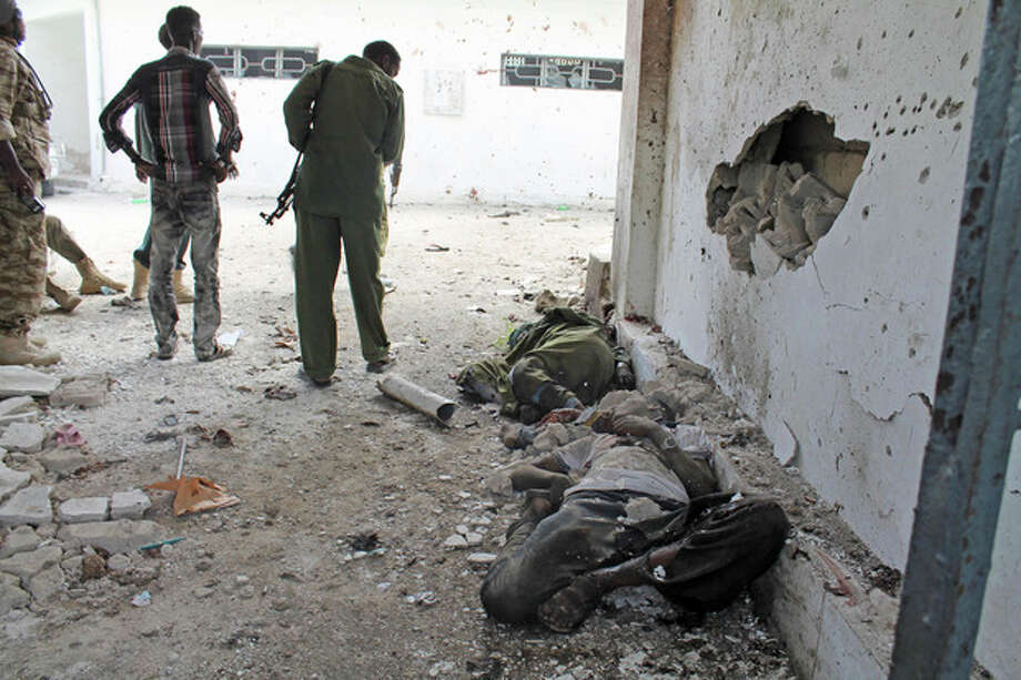 Somali soldiers stand over dead civilians lying at the entrance of Mogadishu's court complex after being killed during a siege by militants in Mogadishu, Somalia, Sunday, April 14, 2013. Militants launched a serious and sustained assault on Mogadishu's main court complex Sunday, detonating at least two blasts, taking an unknown number of hostages and exchanging extended volleys of gunfire with government security forces, witnesses said.(AP Photo/Farah Abdi Warsameh) / AP