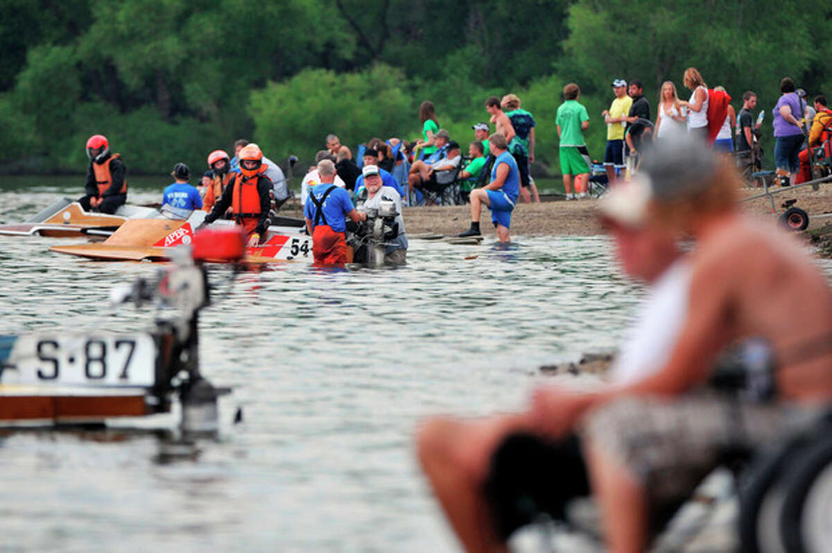 FILE - In this July 30, 2010 photo, competitors and spectators hang out between races on the shore of Lake DePue during the APBA Pro National Championship Boat Races in DePue, Ill. With the severe drought of 2012, about 350 volunteers were needed to create a makeshift dam and get millions of gallons of water pumped into the lake to be able to hold the annual event July 25-29, 2012. The race, the area?'s highlight event of the year, is an economic lifeline for the town of 1,500 people in a less-well-off pocket of Illinois. It brings in millions of dollars and helps buy everything from little league uniforms to equipment for schools. (AP Photo/Journal Star, Patrick Traylor)