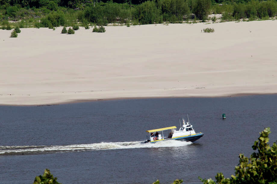 A small boat passes along the Louisiana side of the Mississippi River at Vicksburg, Miss., Thursday, July 26. 2012. in a switch of extremes, the river has dropped to very low levels this summer unlike last year when the river was flooding much of the Delta due to record high levels. The drop in water level now exposes the river bottom, forcing river traffic to a trickle as barges are forced to lessen their loads to keep from getting stuck on sandbars. (AP Photo/Rogelio V. Solis) / AP