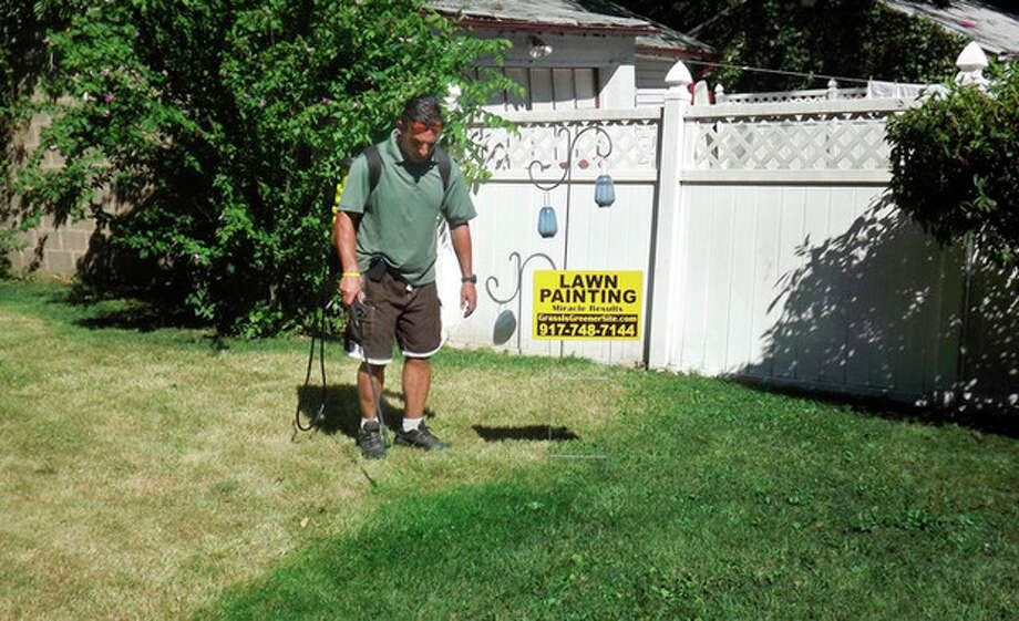 This July 25, 2012 photo provided by Grass is Greener Lawn Painting shows the company's owner, Joseph Perazzo, working on a lawn in Irvington, N.J. With drought spanning about two-thirds of the nation from California to New York, some residents and businesses in normally well-watered areas are taking a page from the lawn-painting practices employed for years in the West and South to give luster to faded turf. (AP Photo/Grass is Greener Lawn Painting) / Grass is Greener
