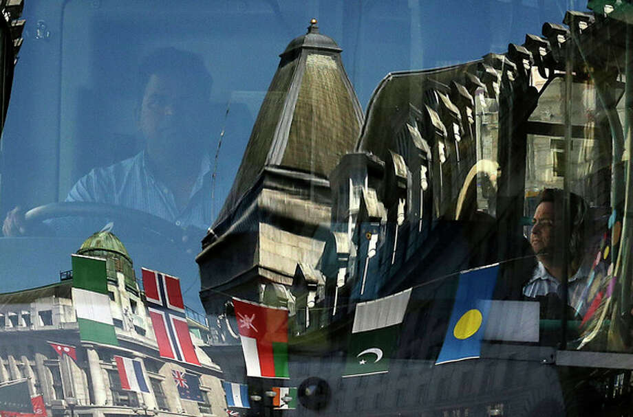 FILE - In this July 24, 2012, file photo, international flags hanging above the street are reflected in a bus' windshield as it travels through central London. The Olympic-sized political gaffes and cultural goofs already registered before the London games officially open Friday have proven one thing in the globalized planet of the early 21st century: Even with the best of intentions, organizing an offense-free Olympics is nearly impossible. (AP Photo/Charlie Riedel, File) / AP