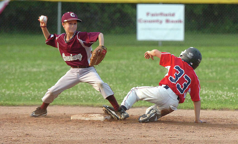 Right, Cranbury's Brendan Edvardsen forces out Norwalk's Shane Popkins at second base. / 2012 The Hour Newspapers