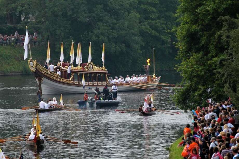 The royal barge Gloriana carries the Olympic flame in a cauldron on board, as it leaves Hampton Court Palace in London, as it makes its way along the river Thames into central London on the final day of the Torch Relay, Friday, July 27, 2012. (AP Photo/Sang Tan) / AP