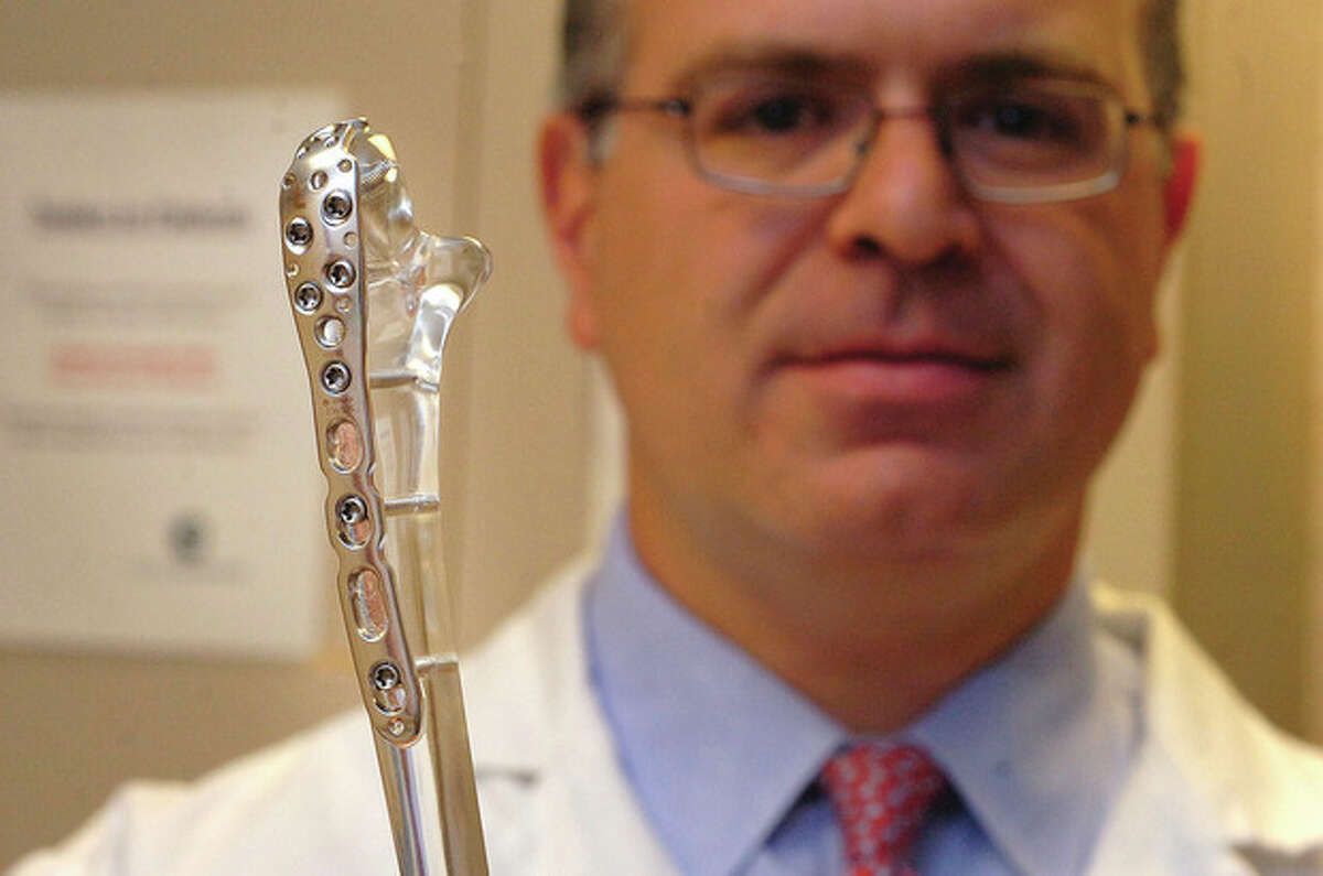 Hour Photo/ Alex von Kleydorff. Dr Michael Soojian M.D. shows some of the hardware now in Troy Strausers right arm