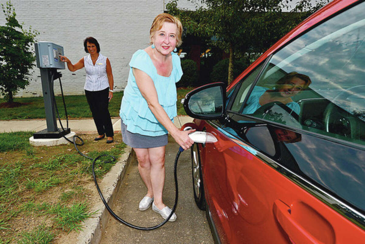 Hour photo / Erik Trautmann Wilton Public Library patron, Eileen Ferro, charges her Chevy Volt at the new charging station as Joan Waldie, library head of building operations, looks on Wednesday.