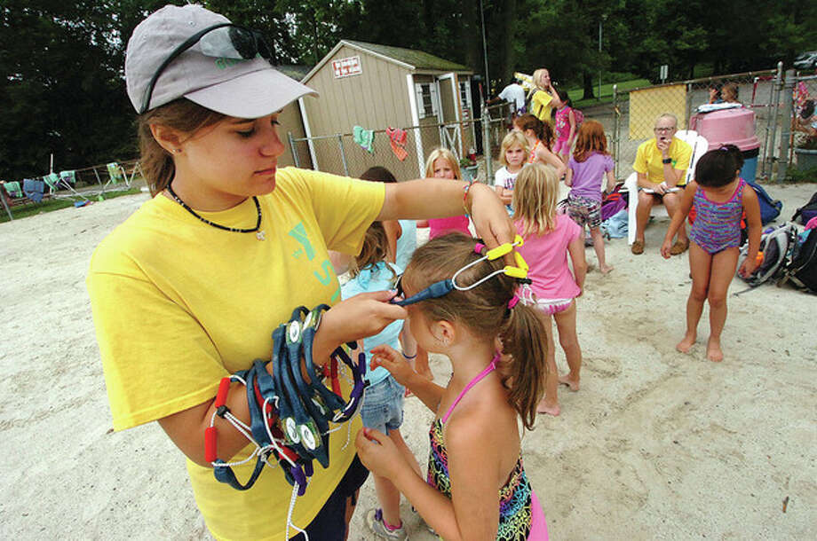 Hour Photo/ Alex von Kleydorff. Wilton Y Counselor Christine Gerhlein places Swimbands on the campers before they go swimming in the pond. / 2012 The Hour Newspapers