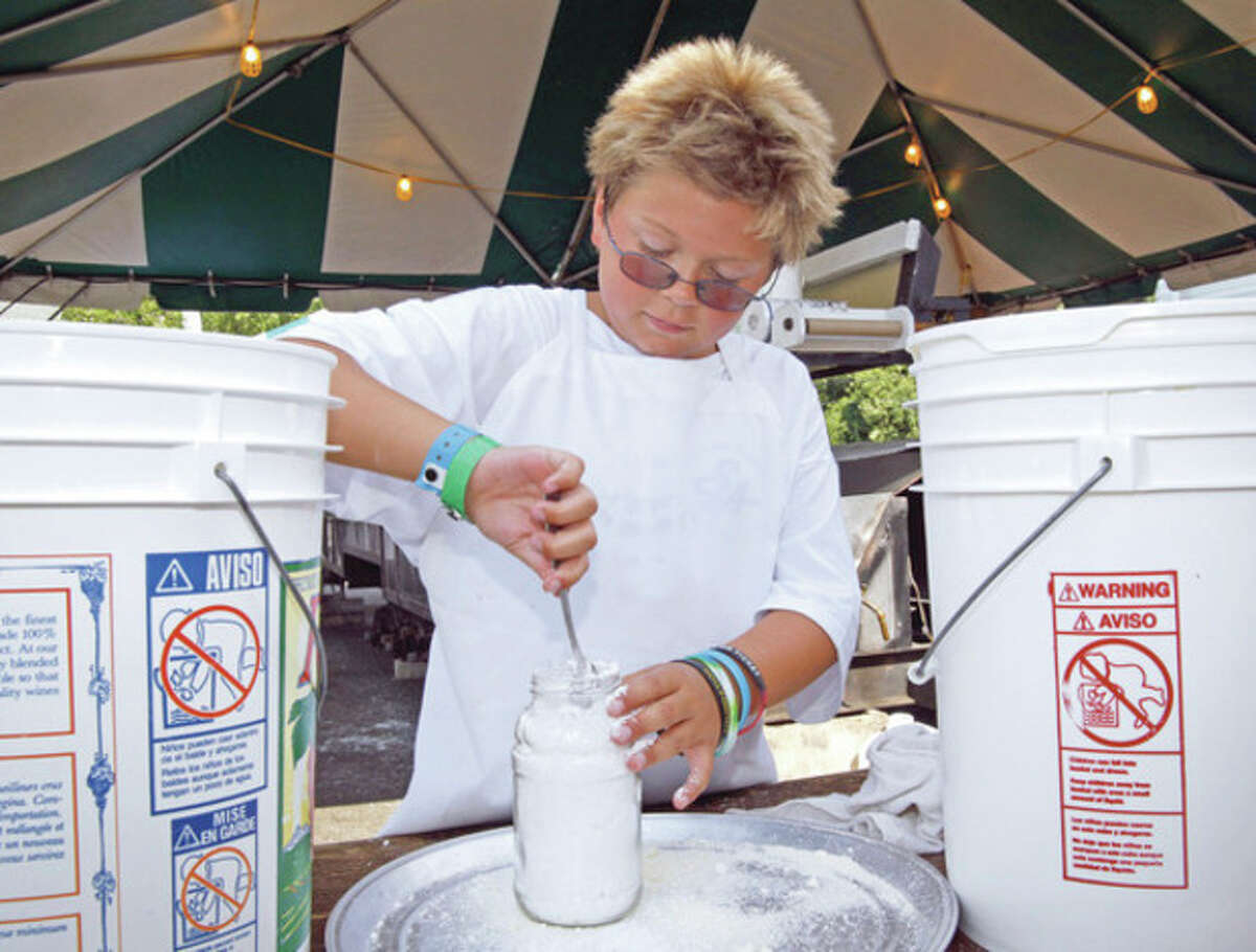 T.J. Boyrer, 11, prepares cheese for pizza fritta during the annual St. Ann's Festival in Norwalk Saturday afternoon. Hour Photo / Danielle Robinson