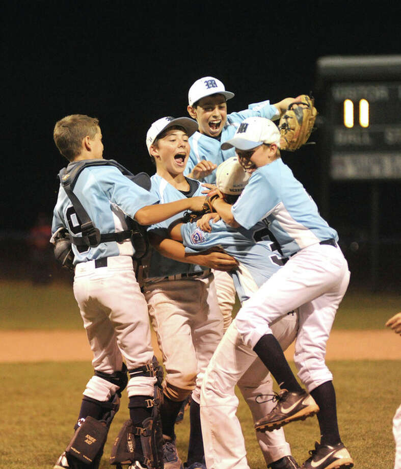 Hour photo/John NashWilton players begin to celebrate the team's 2012 District 1 Little League championship after the final out of its 11-3 win over National Lione at the Springdale Little League Park in Stamford.