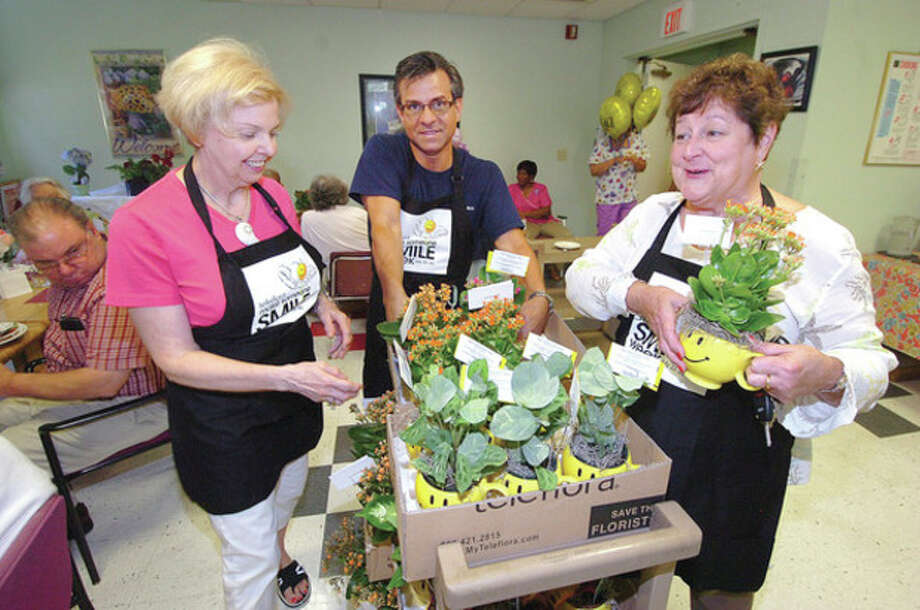 "Hour photo / Alex von KleydorffMake someone smile dayFrom left, Bunnie Hovan with Hovans Florist in Stratford, JP Licari with Licari's Floral Design in Norwalk, and Sue Wall with Hansen's Floral Arts in Fairfield pass around flowers to residents of Ludlow Commons for Teleflora's ""Make someone smile day"" Monday. / 2012 The Hour Newspapers"