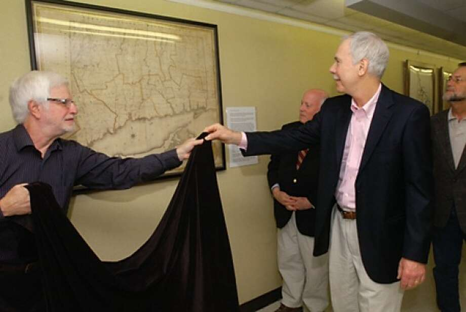 Bob Weingarten, House Research Director at the Westport Historical Society, and Robert Augustyn of Martayan Lan Augustyn Inc. unveil an antique map found by Westporter Carles Reedy, far right, at Town Hall Wednesday while First Selectman Gordon Joseloff looks on. The historic 1812 map of Connecticut whose restoration was funded by Martayan Lan Augustyn Inc. was hung on the first floor of Westport Town Hall outside the Town Clerks office. Hour photo / Erik Trautmann