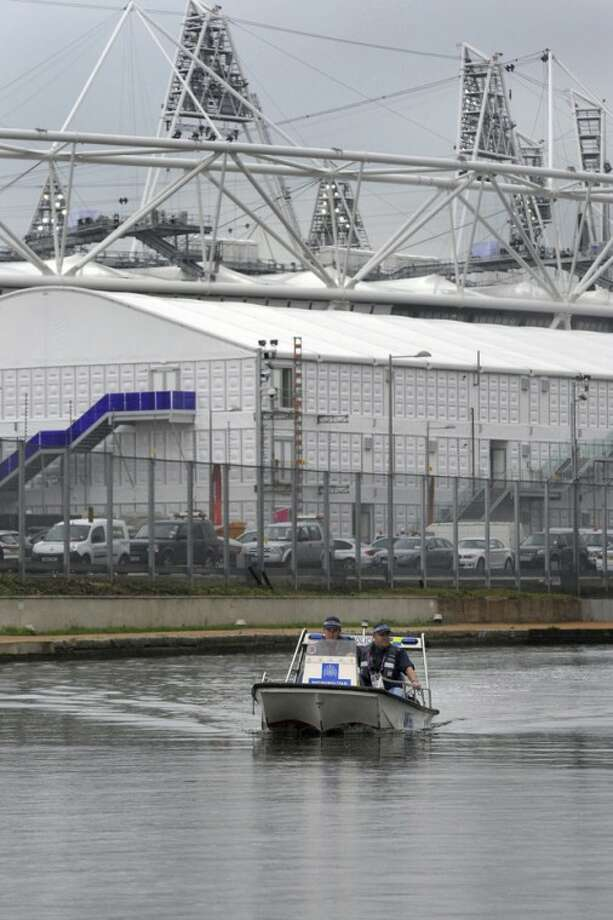 Constable Neil Baker, left, and Constable Dan Collins from the Metropolitan police Marine Unit patrol the canal waterway around the perimeter of the Olympic Stadium in Stratford, east London Friday July 20, 2012. (AP Photo/Anthony Devlin, Pool)