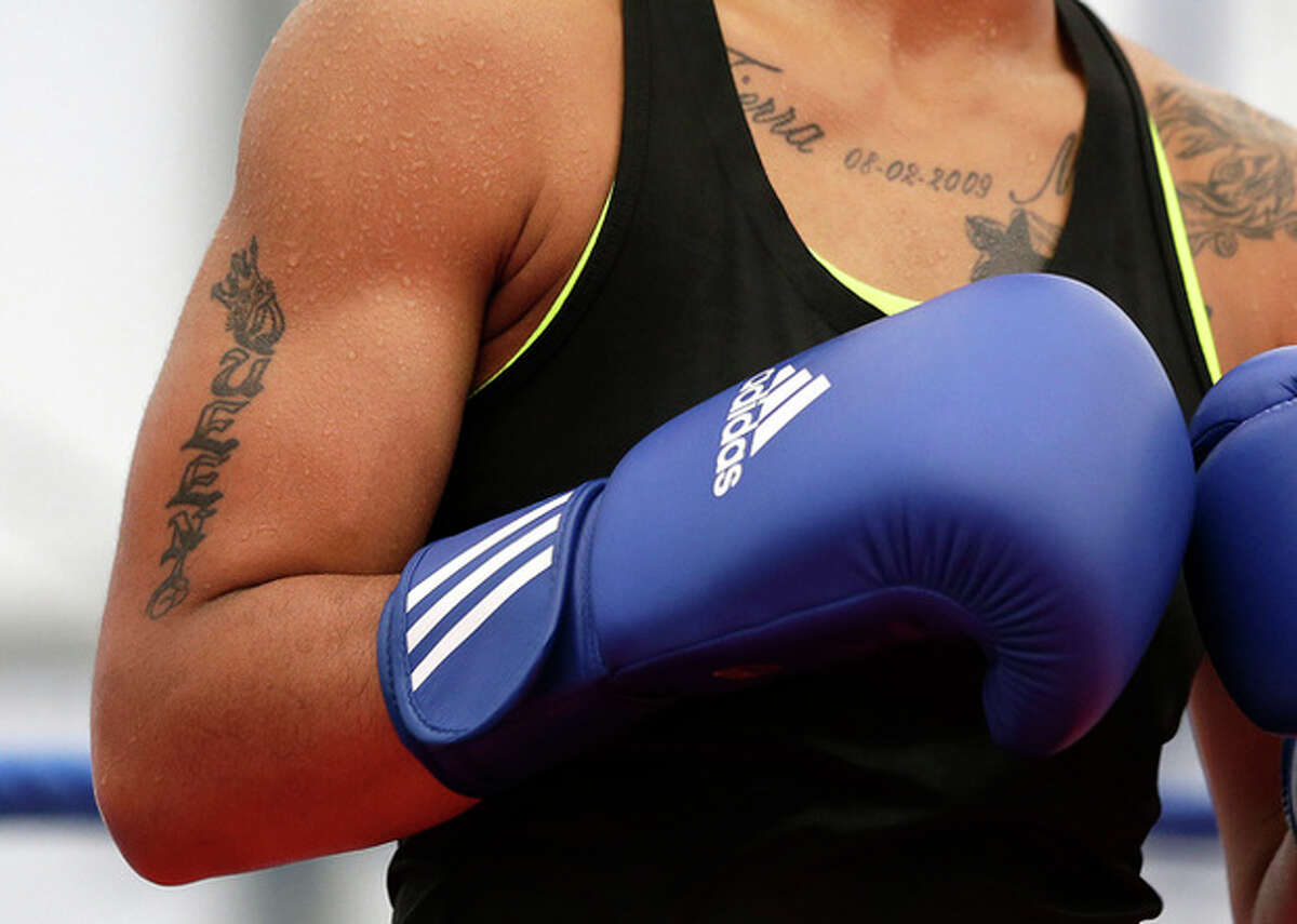 """A tattoo that reads """"Queen"""" is seen on the right arm of United States' 60-kg lightweight boxer Queen Underwood during a practice session at the 2012 Summer Olympics, Thursday, July 26, 2012, in London. (AP Photo/Patrick Semansky)"""