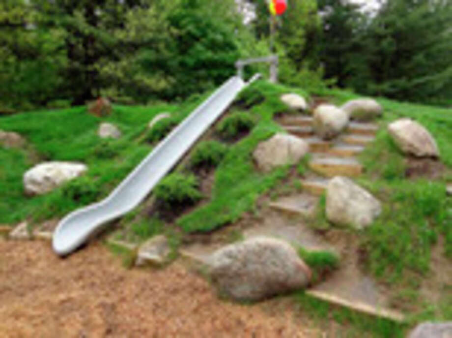 In this publicity photo provided by Natural Playgrounds Company, an embankment slide is built into a constructed hill at an elementary school as shown here in Glens Falls, N.Y. The embankment slide is safer than tower slides with ladders. Scattered boulders, random dirt steps, rough terrain, and varied plantings add to the rich textures and varied experiences on Natural Playgrounds. (AP Photo/Natural Playgrounds Company) / Natural Playgrounds Company