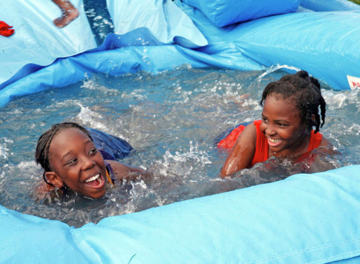 Kani Cook, 11 and Aaliyah Detolline, 8, play in the water during the annual Hatian Fesitval at Veteran's Park in Norwalk Saturday afternoon.
