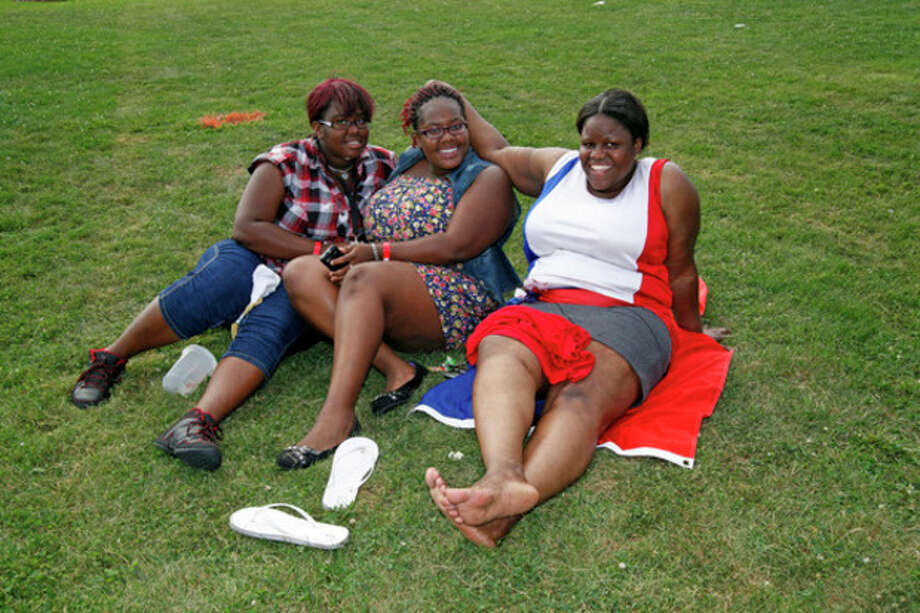 Henryiana Maxelix, Katarica Maxelix and Elda Jeudy listen to music during the annual Hatian Fesitval at Veteran's Park in Norwalk Saturday afternoon.