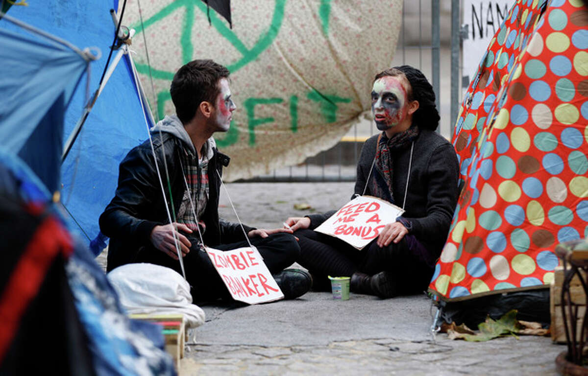 Protestors dressed as zombies are seen outside St Paul's Cathedral in London, Monday, Oct. 31, 2011. The Dean of the cathedral, The Very Reverend Graeme Knowles resigned Monday amid criticism of the handling of the Occupy London protests. (AP Photo/Kirsty Wigglesworth)