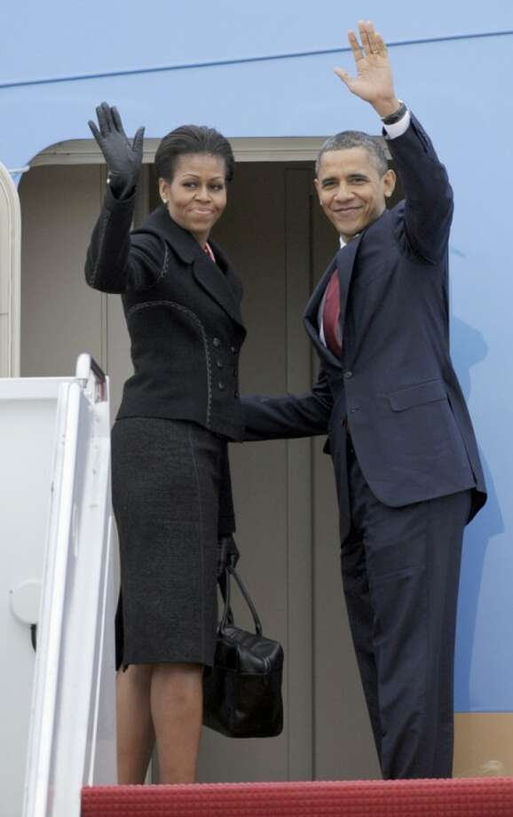 President Barack Obama and first lady Michelle Obama wave prior to boarding Air Force One at Andrews Air Force Base, Md., Wednesday, Dec. 14, 2011. (AP Photo/Cliff Owen)