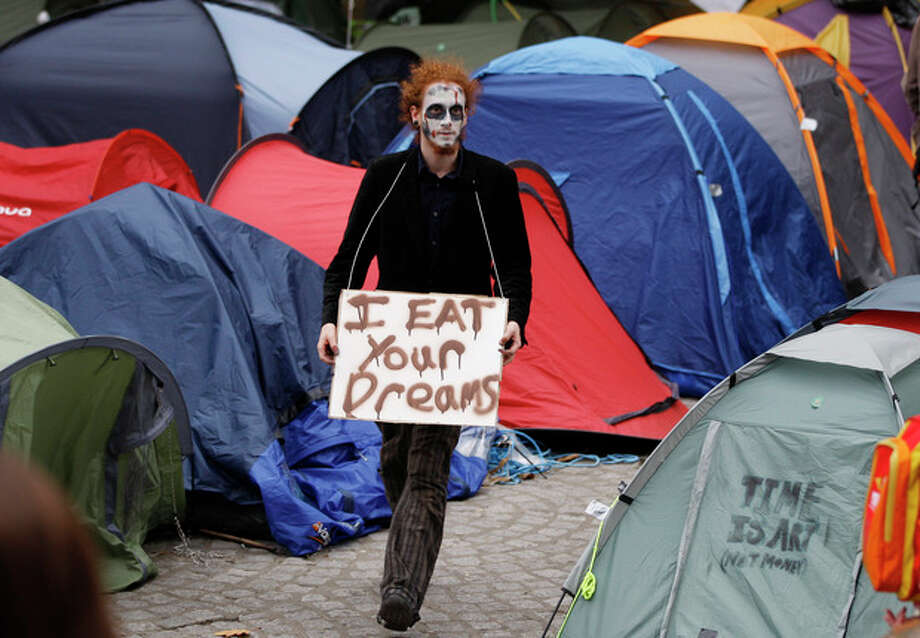 A protestor dressed as a zombie walks past tents outside St. Paul's Cathedral in London, Monday, Oct. 31, 2011. The Dean of St. Paul's Cathedral in London on Monday became the second high-profile clergy member to step down amid mounting controversy over anti-capitalist protests on the church's grounds. (AP Photo/Kirsty Wigglesworth) / AP