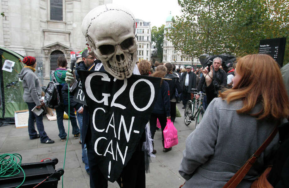 A woman reacts as a protestor wearing a skeleton mask walks past her outside St. Paul's Cathedral in London, Monday, Oct. 31, 2011. The Dean of St. Paul's Cathedral in London on Monday became the second high-profile clergy member to step down amid mounting controversy over anti-capitalist protests on the church's grounds. (AP Photo/Kirsty Wigglesworth) / AP