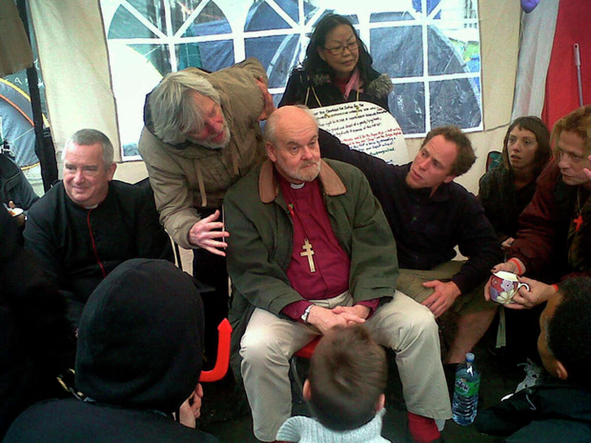 """The Right Reverend Richard Chartres, Bishop of London, center, and Dean of St Paul's Cathedral, The Right Reverend Graham Knowles, left, meet a select group from the Occupy London movement in """"the tea tent"""" at St Paul's before addressing protesters on the steps of the cathedral Sunday Oct. 30, 2011. The Bishop of London says anti-capitalist demonstrators camped outside the city's iconic St. Paul's Cathedral have said they will likely move on. Both the church and the local authority, the City of London Corporation, have launched legal action to seek to clear the scores of tents from a pedestrianized square and footpath outside the cathedral. (AP Photo/Arj Singh/PA Wire) UNITED KINGDOM OUT NO SALES NO ARCHIVE"""