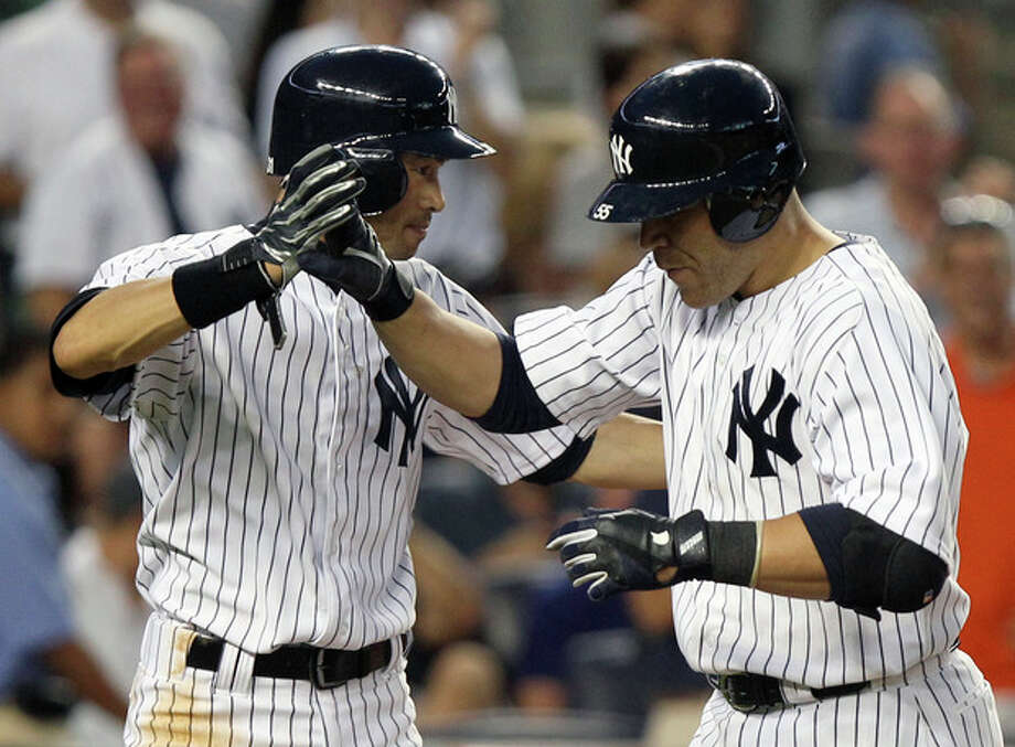New York Yankees' Russell Martin, right, is greeted by teammate Ichiro Suzuki after hitting a two-run home run during the fourth inning of a baseball game against the Boston Red Sox at Yankee Stadium in New York, Friday, July 27, 2012. (AP Photo/Seth Wenig) / AP