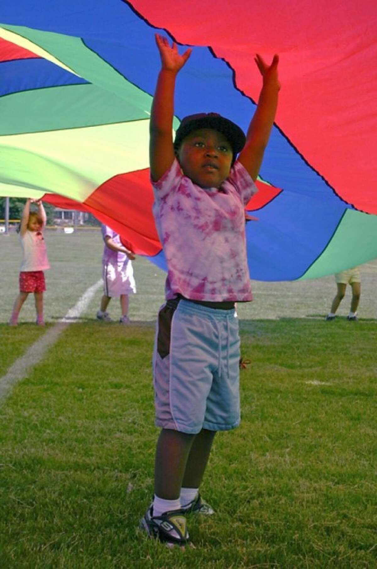 Omega Smith takes the oppertunity to run under a rainbow colored sheet during the Side by Side Charter schools feild day, in Norwalk on Friday morning. Hour Photo / Lucina Sinclair