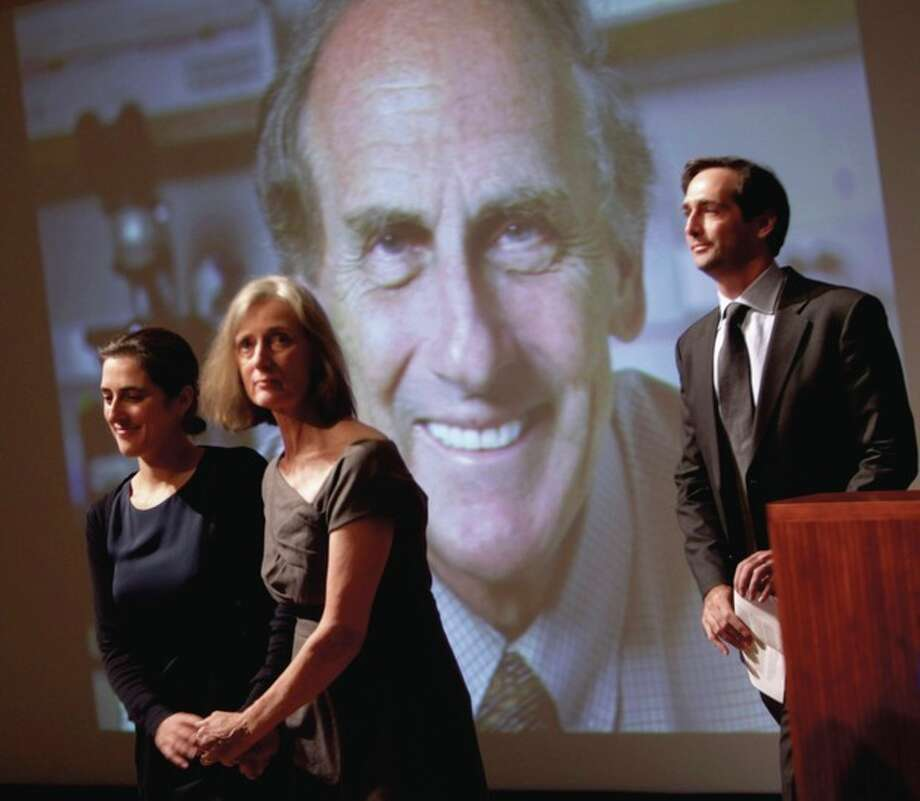 AP photo / Seth Wenig Family members of Nobel prize winner Ralph Steinman walk in front of a picture of Steinman during a ceremony honoring him at Rockefeller University in New York, Monday. From left to right are daughter Lesley Steinman, wife Claudia Steinman and son Adam Steinman. / AP