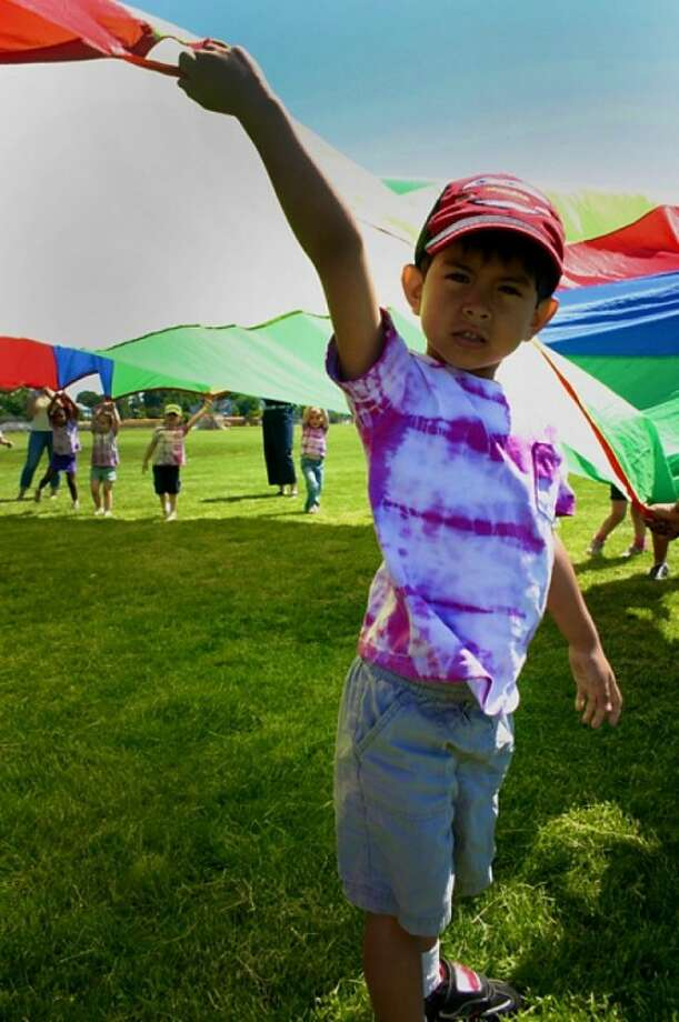 Ander Aguilar of Side by Side Charter school holds up a rainbow sheet during a feild day in Norwalk on Friday morning. Hour Photo / Lucina Sinclair