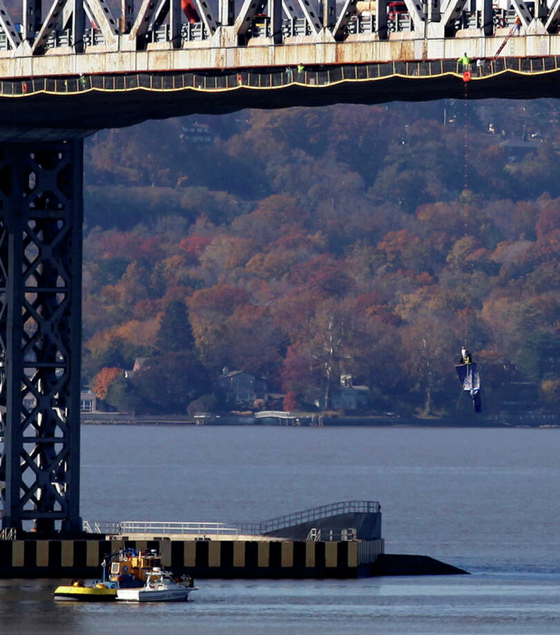 """A man dangles from the Tappan Zee Bridge near Tarrytown, N.Y., Monday, Nov. 7, 2011, holding a sign accusing Rockland County officials of a """"cover-up,"""" according to The Journal News. Rockland County spokesman Ron Levine says the man is a former employee with the county's department of mental health who was let go because he was unable to perform his duties. Levine says he is unsure of the man's complaints. (AP Photo/Craig Ruttle) / FR61802 AP"""