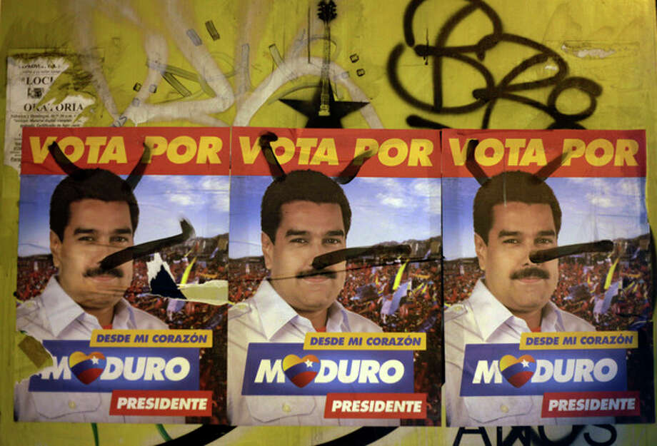 Defaced campaign signs of ruling party presidential candidate Nicolas Maduro cover a wall in Caracas, Venezuela, Friday, April 12, 2013. Maduro, who served as Chavez's foreign minister and vice president, is running against opposition candidate Henrique Capriles in Sunday's presidential election. (AP Photo/Ariana Cubillos) / AP