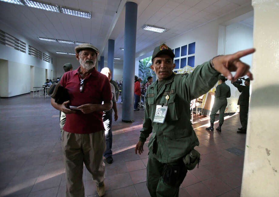 A voter gets directions from a soldier on where to cast his ballot in the presidential election at a polling station in Caracas, Venezuela, early Sunday, April 14, 2013. Interim President Nicolas Maduro, who served as the late Hugo Chavez's foreign minister and vice president, is running against opposition candidate Henrique Capriles. (AP Photo/Fernando Llano) / AP
